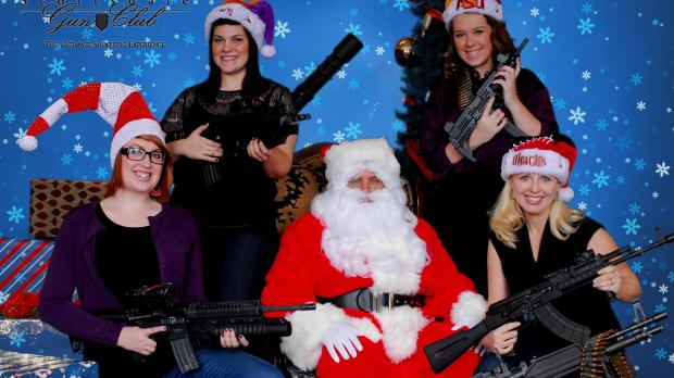 This undated image provided by the Scottsdale Gun Club shows people posing with Santa Claus and several guns. Photo: Scottsdale Gun Club, Gordon Murray