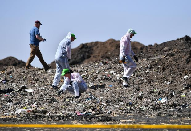 Forensic experts work at the crash site of the Ethiopian Airlines operated Boeing 737 MAX aircraft.