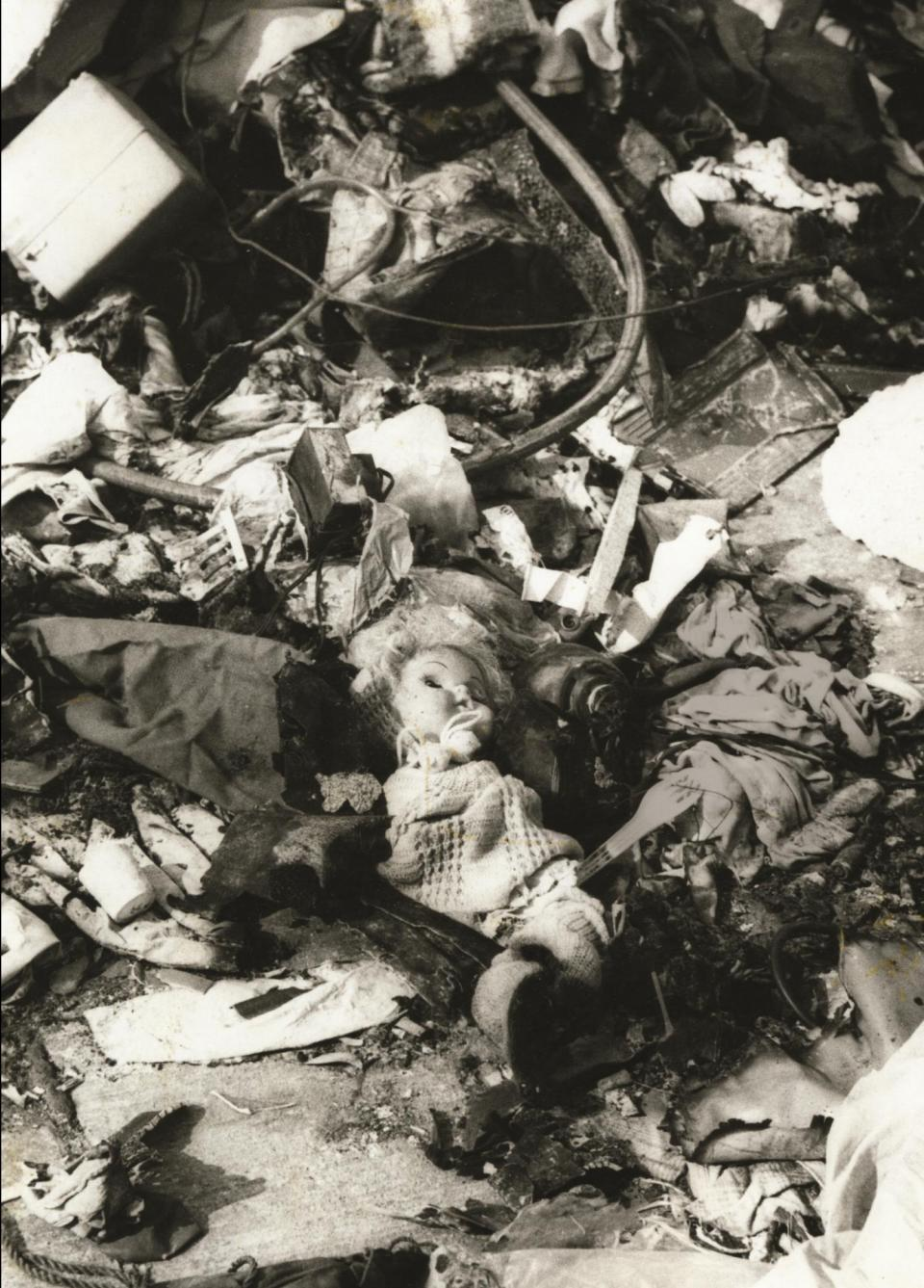 A doll lies among the burnt wreckage.