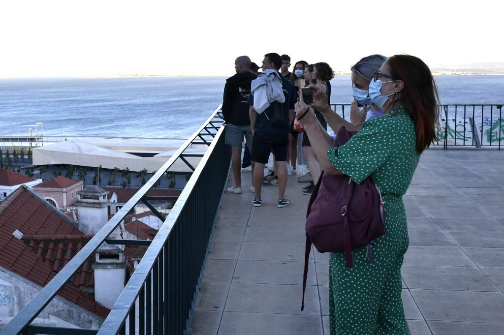 Several tourists wearing protective masks walk near the viewpoint of Porta do Sol, Lisbon, Portugal on 4 August 2020. Photo: AFP
