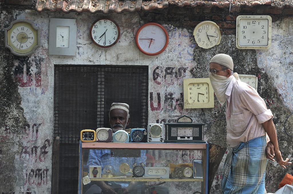 A watchmaker waits for customers in Chennai, India. Photo: AFP