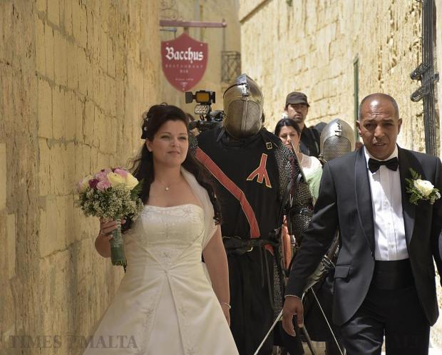 A newly-wed couple walk through the streets of Mdina with re-enactors behind them at the Medieval Mdina Festival on April 23. Photo: Mark Zammit Cordina