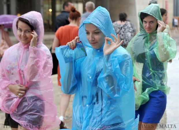 Tourists wear disposable anoraks during the downpour in Valletta on September 9. Photo: Chris Sant Fournier