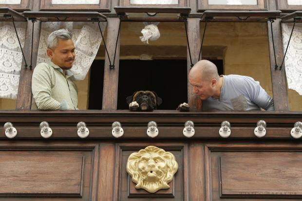 Two men and a dog wait in a balcony for a statue of the Risen Christ to be carried past their house during an Easter Sunday procession in Cospicua, on April 5. Photo: Darrin Zammit Lupi