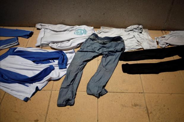 Clothes of migrants are seen laid out to dry outside an overcrowded sport center after arriving on a rescue boat at the port of Tarifa.