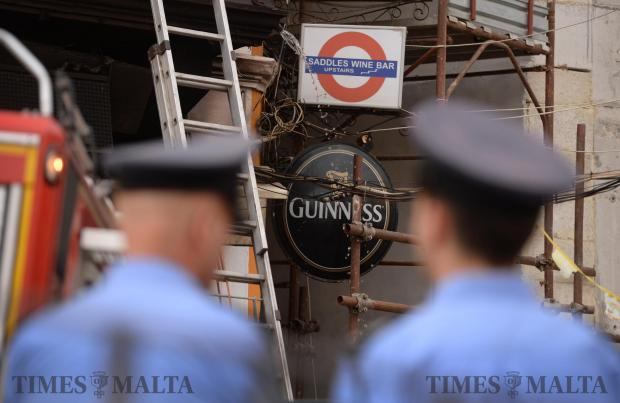 Two policemen wait for a fire to be extinguished at Saddles Bar in Spinola on May 11. Photo: Matthew Mirabelli