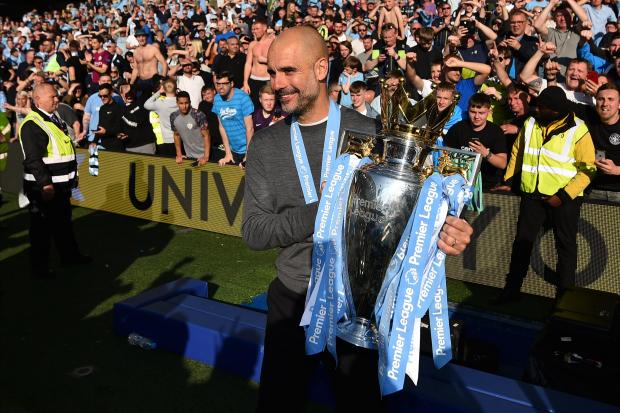 Manchester City's Spanish manager Pep Guardiola poses with the Premier League trophy.