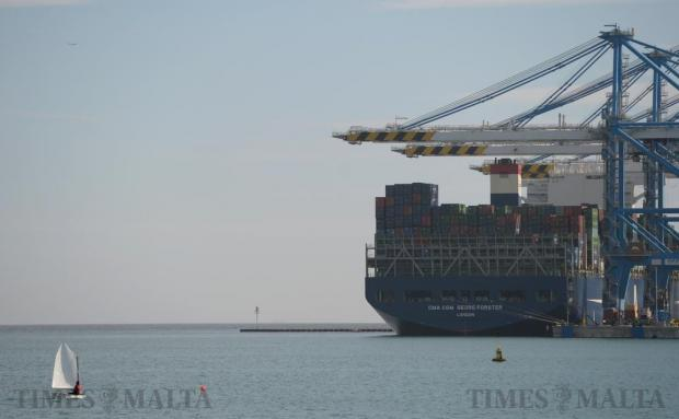 A small sailing dinghy is dwarfed by a large container ship in Birzebbugia on January 9. Photo: Matthew Mirabelli