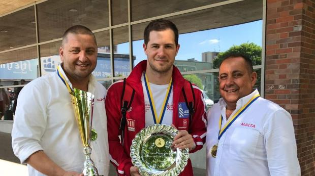 Jordan Camilleri holds the MVP trophy with Malta coach Karl Izzo (left) and his assistant Anthony Farrugia.