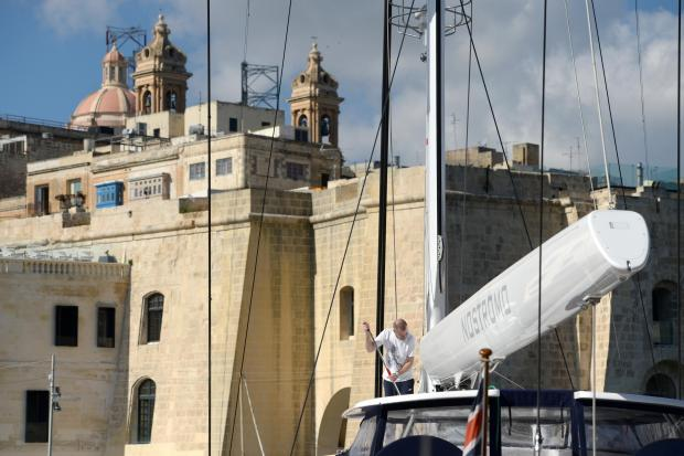A man cleans the deck of a luxury superyacht at the Grand Harbour Marina on Birgu on January 30. Photo: Matthew Mirabelli