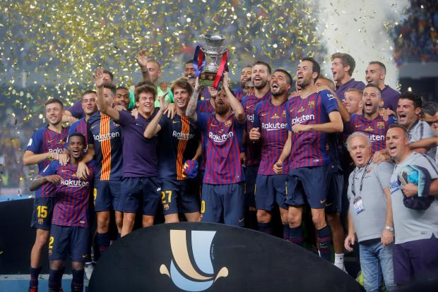 Barcelona's Lionel Messi lifts the trophy as he celebrates winning the Spanish Super Cup with team mates.
