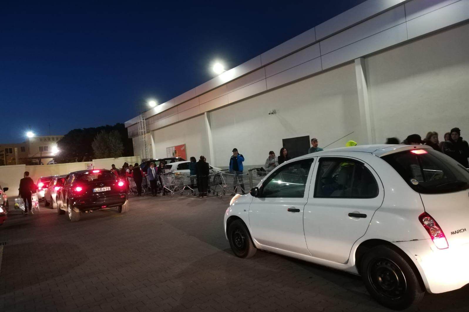 Shoppers waiting to enter a Lidl supermarket.