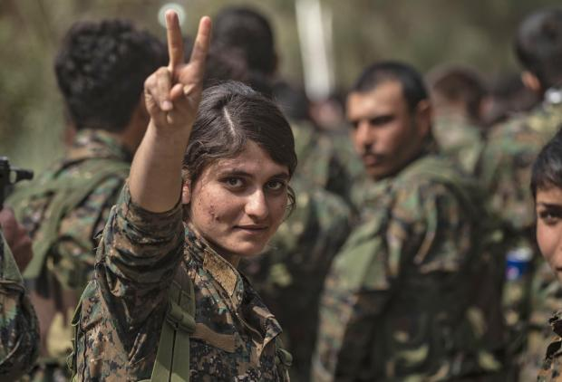 A female fighter of the US-backed Kurdish-led Syrian Democratic Forces (SDF) flashes the victory gesture while celebrating near the Omar oil field in the eastern Syrian Deir Ezzor province.