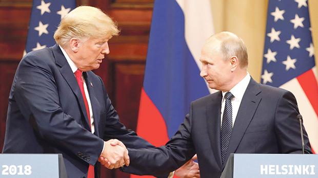 US President Donald Trump and Russian President Vladimir Putin shake hands as they hold a joint news conference after their meeting in Helsinki, Finland. Photo: Grigory Dukor/Reuters