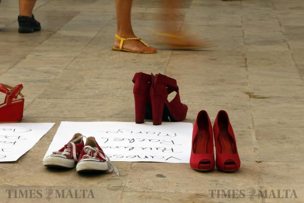 Pairs of red shoes, symbols of the struggle for women's rights, are left on the ground next to posters with the names of women murdered in extreme acts of domestic violence during a protest outside parliament in Valletta on July 12. Photo: Darrin Zammit Lupi