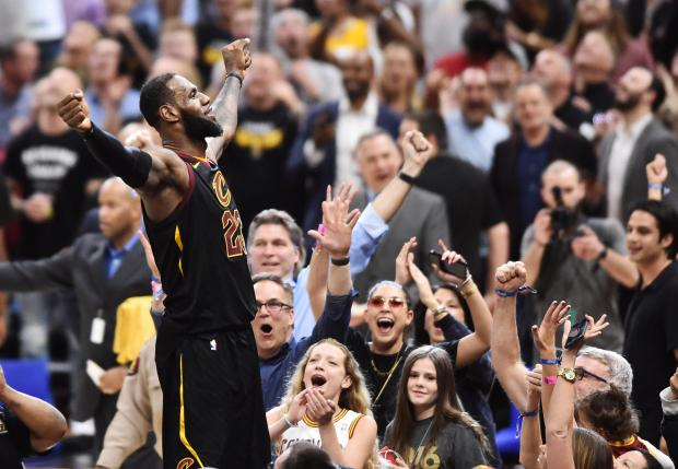Cleveland Cavaliers forward LeBron James (23) stands on the scorer's table after hitting the final shot to win the game against the Toronto Raptors in game three of the second round of the 2018 NBA Playoffs at Quicken Loans Arena. Photo Credit: Ken Blaze-USA TODAY Sports