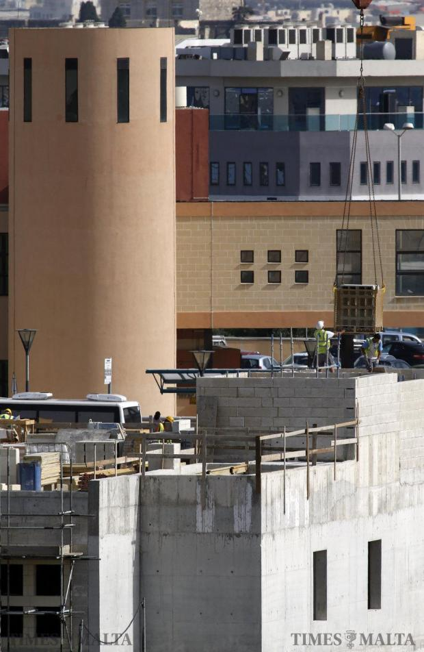 A construction worker reaches out for a stack of concrete bricks as it is lowered onto a building site at Mater Dei Hospital on May 20. When it was established that the structures of the Accident and Emergency department were too weak to take nay further weight, the government had to shift the location of its original 68-bed, two-floor project to another site on the hospital grounds at Tal-Qroqq. Photo: Darrin Zammit Lupi