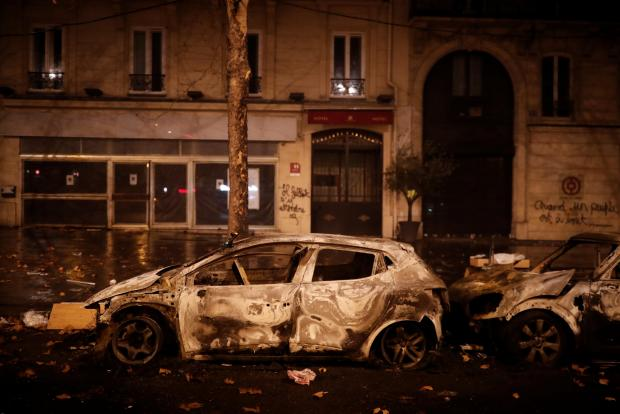 Burned cars are seen in a street near the Place de l'Etoile. Photo: Reuters