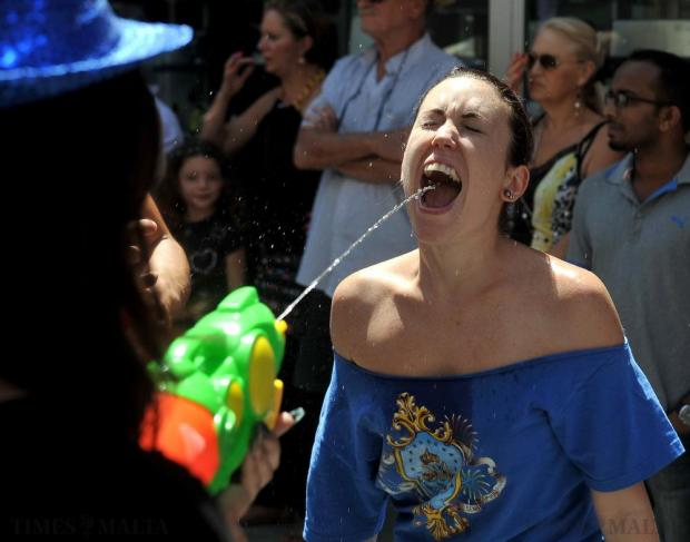 A girl takes a drink from a water pistol during the Santa Marija march in Mosta on August 15. Photo: Chris Sant Fournier