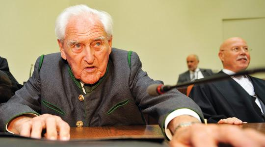 Former commander of a German mountain infantry battalion Josef Scheungraber (left) sits with his lawyer Rainer Thesen (right) in the regional court in the southern German city of Munich yesterday during the announcement of his verdict.