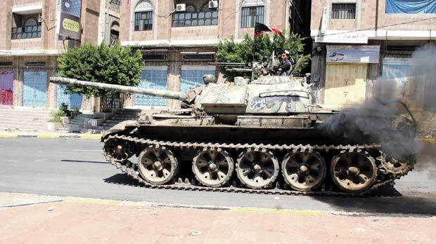 A pro-government fighter rides on a tank during clashes with Houthi fighters in Yemen's southwestern city of Taiz, yesterday.