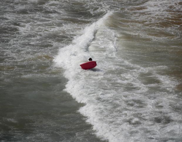A woman holding a red surf board makes her way to the waves at Għajn Tuffieħa on July 16. Photo: Mark Zammit Cordina