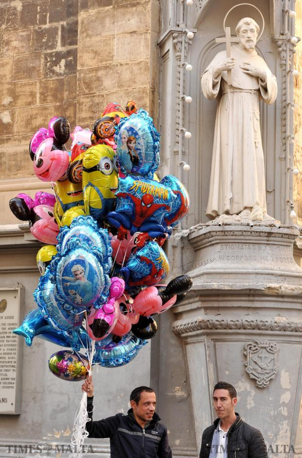Two men have a chat while holding balloons in Republic Street, Valletta on February 8. Photo: Chris Sant Fournier