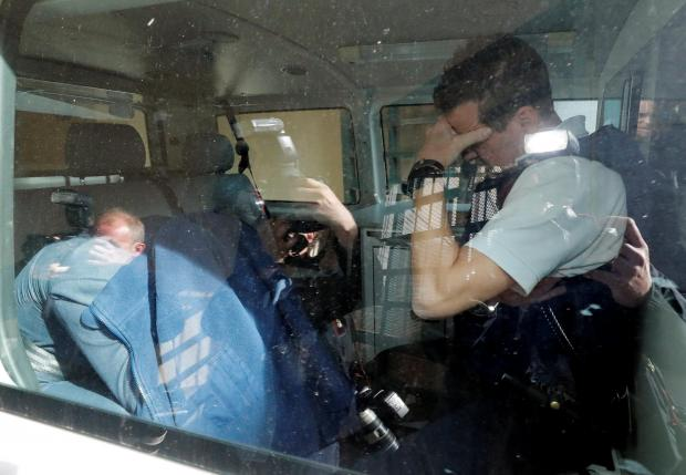 Referee Bart Vertenten hides under a jacket as he leaves the courthouse in Tongeren