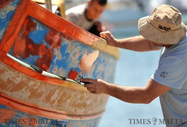 A man paints his luzzu in Marsaxlokk on April 18. Photo: Chris Sant Fournier