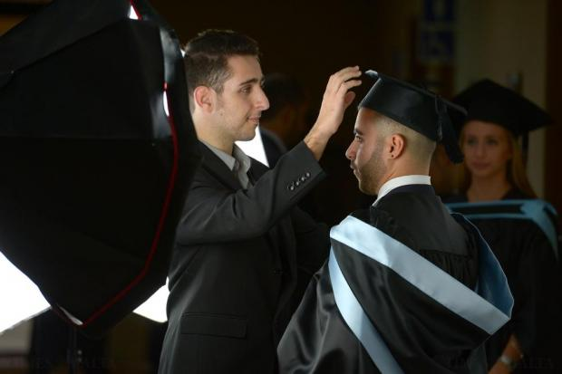 A graduate is prepared for his official photograph after graduating in Business and Information Technology at the University of Malta on November 23. Photo: Matthew Mirabelli