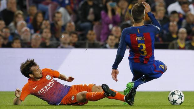Barcelona's Gerard Pique is fouled by Manchester City's David Silva. Photo: Albert Gea, Reuters