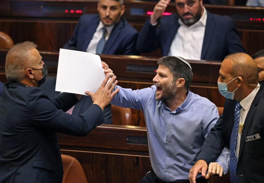 Israeli far-right lawmaker Bezalel Smotrich, head of the Religious Zionism party, gestures with placards. Photo: AFP