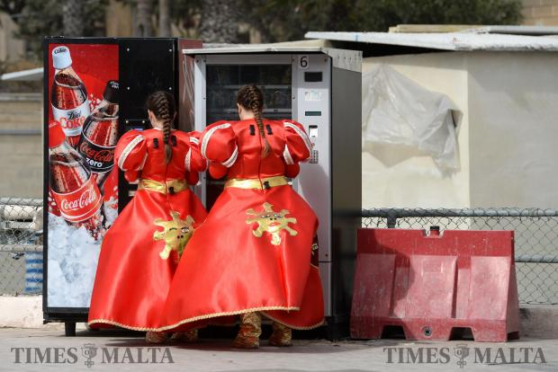 Two girls dressed in carnival costume stop for a quick drink in Floriana on February 27. Photo: Matthew Mirabelli