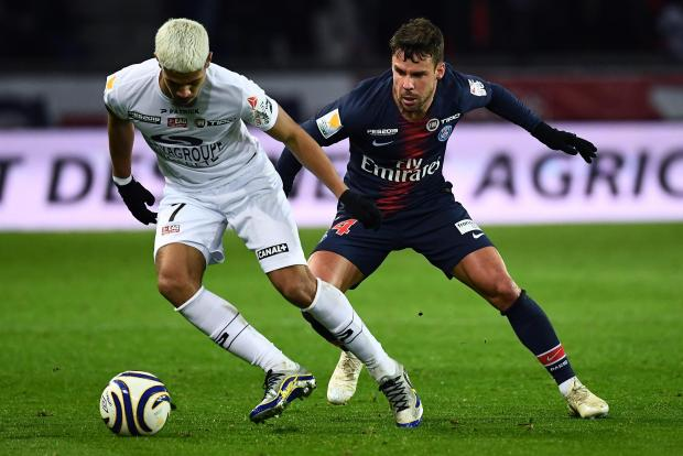 Guingamp's French midfielder Ludovic Blas (L) vies for the ball with Paris Saint-Germain's Spanish defender Juan Bernat.
