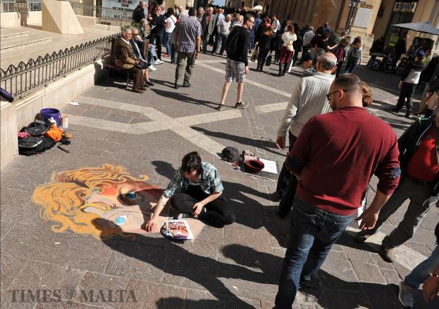 Passers by look at a street artist as she creates a portrait on the Valletta pavement on March 1. Photo: Chris Sant Fournier