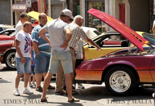 A group of men admire the shiny engine of one of the cars at the Hamrun Car Show on May 27. Photo: Chris Sant Fournier