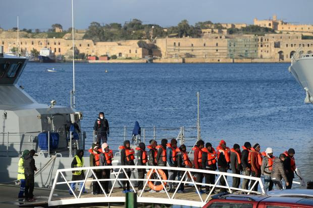 Migrants, part of a group of 49, disembark from one of Malta's AFM Protector-class coastal patrol boats on January 9, 2019 after being transfered from the Dutch-flagged rescue Vessel Sea Watch 3 to Haywharf in Valletta,
