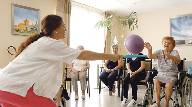 A resident tosses a ball through a hoop held by ACTive Age Malta facilitator Charlotte Stafrace.