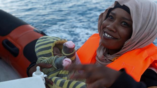 A Somali migrant carries her 12-day-old baby on board a rigid-hulled inflatable boat. (Darrin Zammit Lupi)