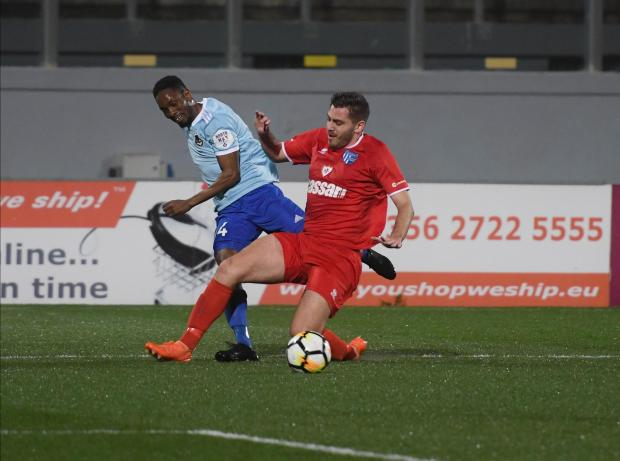 Frank Temile of Sliema Wanderers attempts a cross despite being tackled by Tarxien Rainbows' Luke Grech. Photo: Jonathan Borg