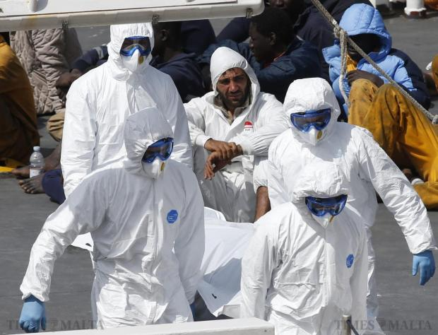 Mohammed Ali Malek (centre, rear), one of two survivors of Saturday's migrant boat disaster, later arrested on suspicion of people trafficking, is seen watching bodies of dead migrants being disembarked from the Italian coastguard ship Bruno Gregoretti, at Senglea on April 20. Italian authorities arrested two survivors of Sunday's migrant boat disaster on suspicion of people trafficking, Infrastructure Minister Graziano Delrio said on Tuesday after the men arrived in the Sicilian port of Catania. Photo: Darrin Zammit Lupi