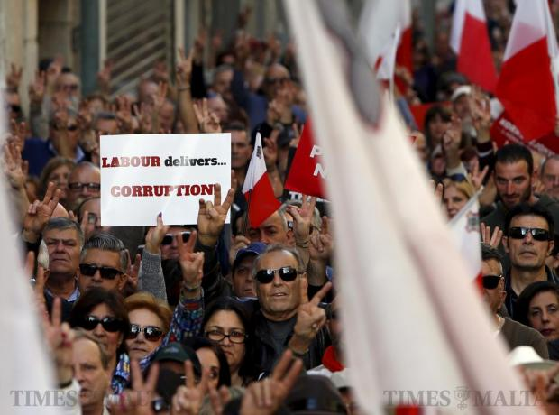 Protestors make victory gestures as the national anthem is played at the end of a demonstration against alleged government corruption in Valletta on March 6. Photo: Darrin Zammit Lupi