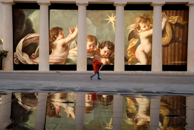 A little girl walks past a painting reflected in St George's Square in Valletta on December 5. Photo: Matthew Mirabelli