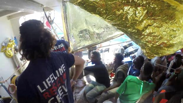 Migrants and crew are seen on the ship Lifeline while the Malta Armed Forces deliver aid, near Malta.