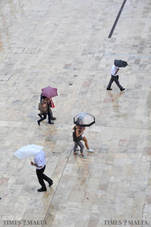 Passers by take shelter under umbrellas during a downpour in Valletta on September 9. Photo: Chris Sant Fournier