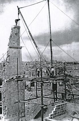 The remains of the ancient tower being demolished in 1949 in very risky conditions. Note the man standing dangerously on the top.
