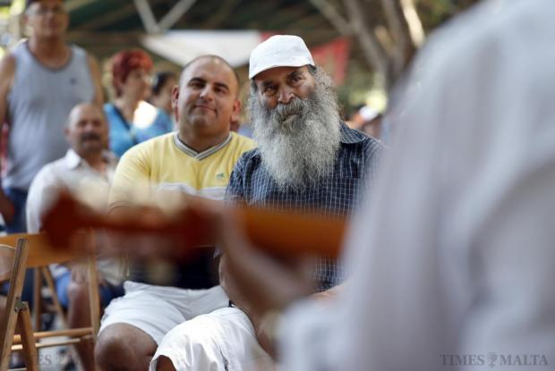 People watch folk musicians performing during the agricultural festival of L-Imnarja in Buskett Gardens on June 29. L-Imnarja, also known as the feast of St. Peter and St. Paul, is the most important date in the Maltese folklore diary. Photo: Darrin Zammit Lupi