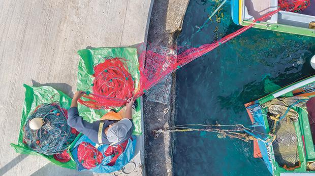 A fisherman at Marsalforn harbour gathering his multicoloured nets.