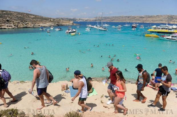 Bathers roam at the Blue Lagoon on Comino after MTA officials clamped on beach operators' abusive practice of filling every available space with deckchairs and umbrellas on August 17. Photo: Steve Zammit Lupi