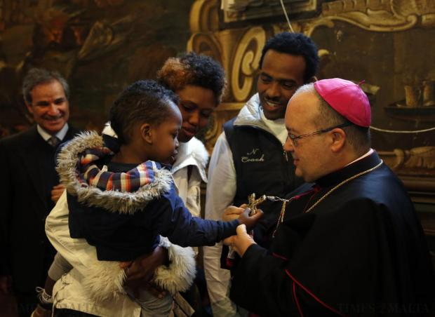An Eritrean child takes hold of Apostolic Administrator Charles Scicluna's crucifix during an exchange of greetings at the Curia in Floriana on December 28. Photo: Darrin Zammit Lupi